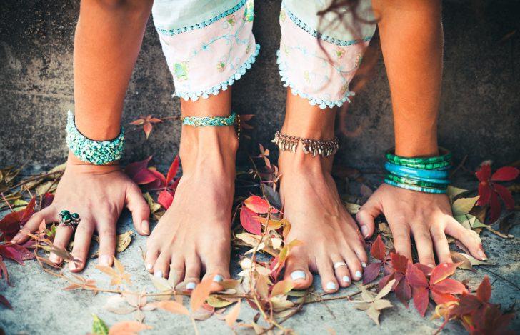 落ち葉の上で裸足で前屈をしている女性の足もとだけ