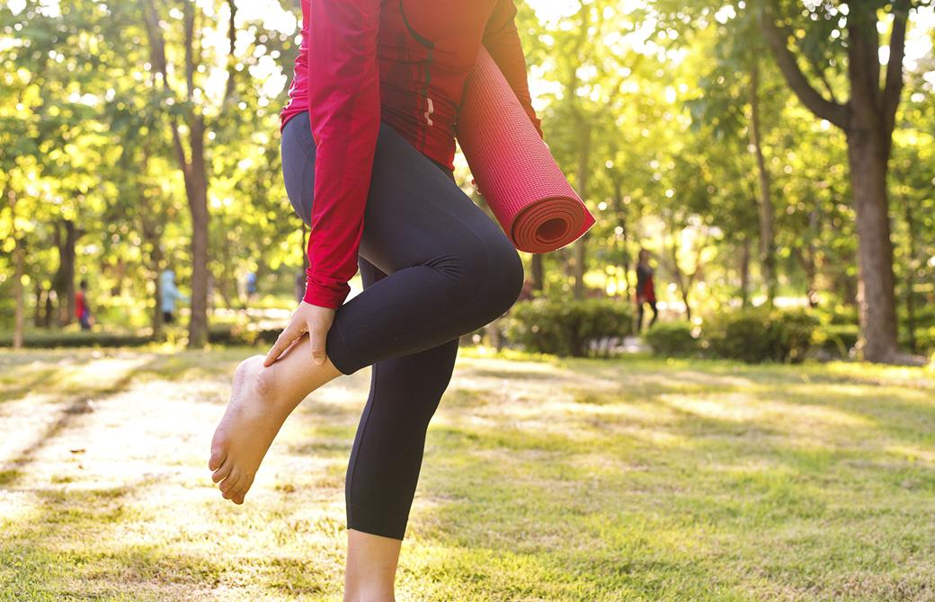 公園でヨガマットを持った女性が片足を持ち上げて足首を気にかけている