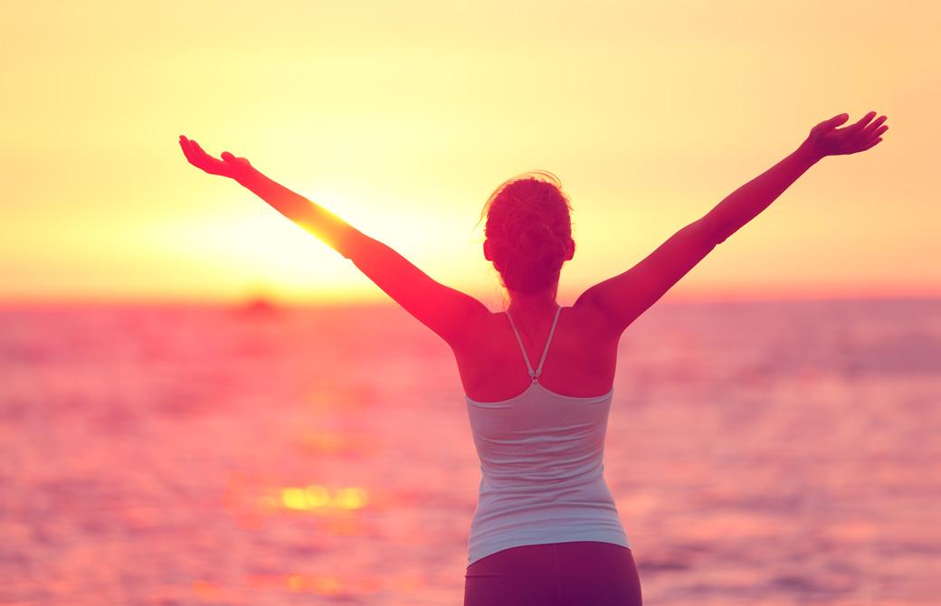 夕陽の沈む海辺で両腕を挙げている女性