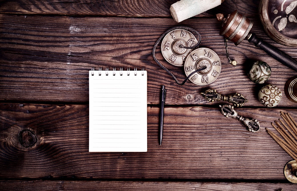 テーブルの上にティンシャなどヨガグッズが並べられノートとペンが置かれている