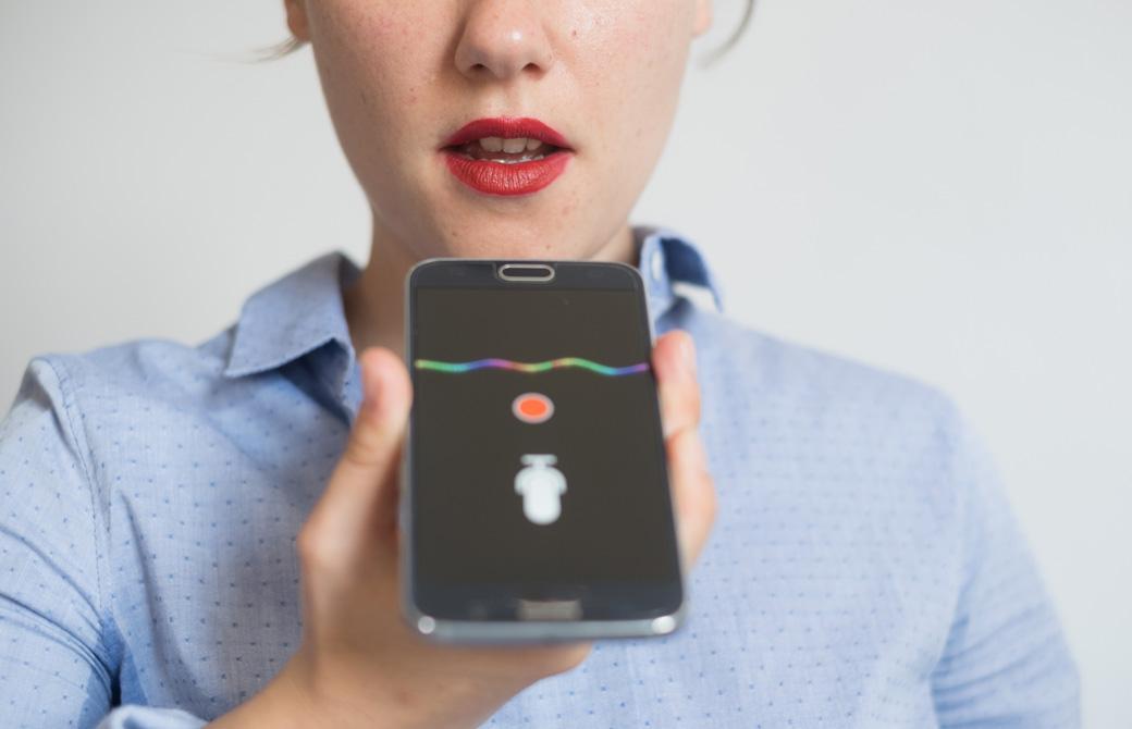 スマートフォンに向って自分の声を録音している女性