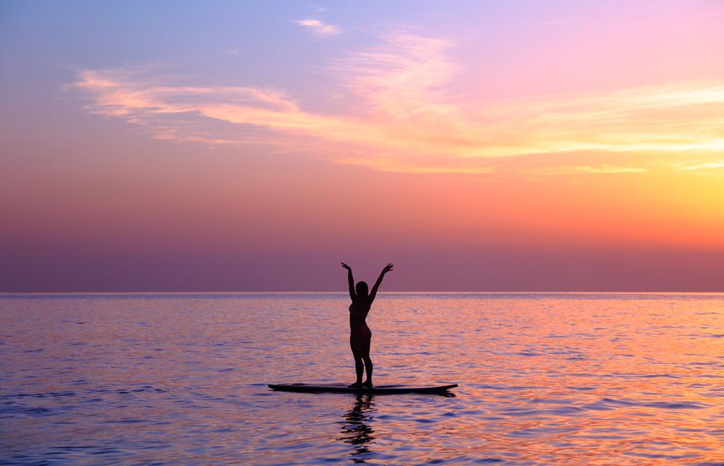 夕焼けの波のないビーチでサーフボードに乗って伸びをしている女性のシルエット