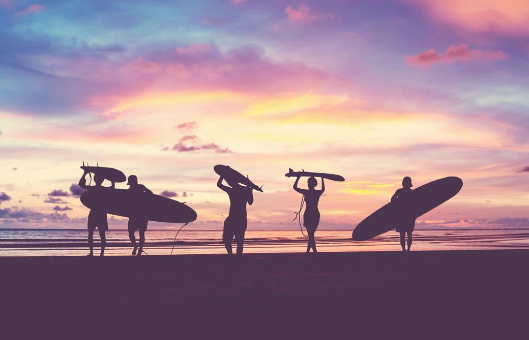 サーフボードを抱えたサーファーたちが夕焼けの浜辺で佇んでいる