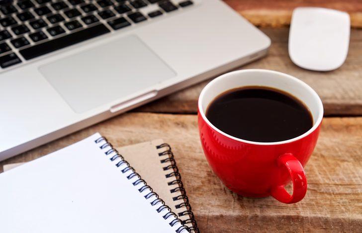 PCとコーヒーとノートが机の上にある写真