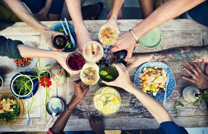 パーティーテーブルでグラスを合わせる人たち