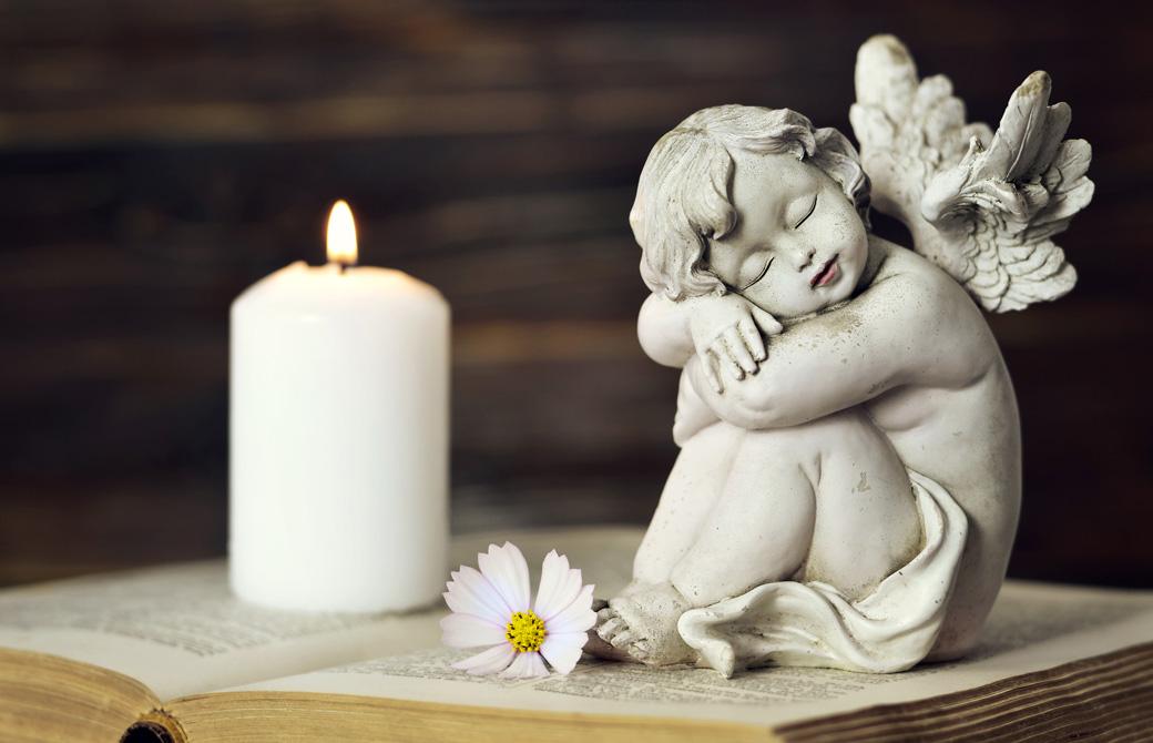 開かれた本の上に天使の置物とキャンドルが灯っている