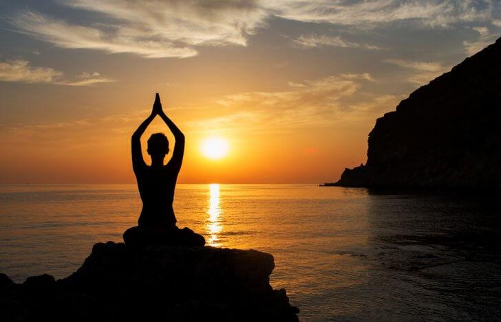 インドのゴアで夕日に向かって瞑想をしている女性のシルエット