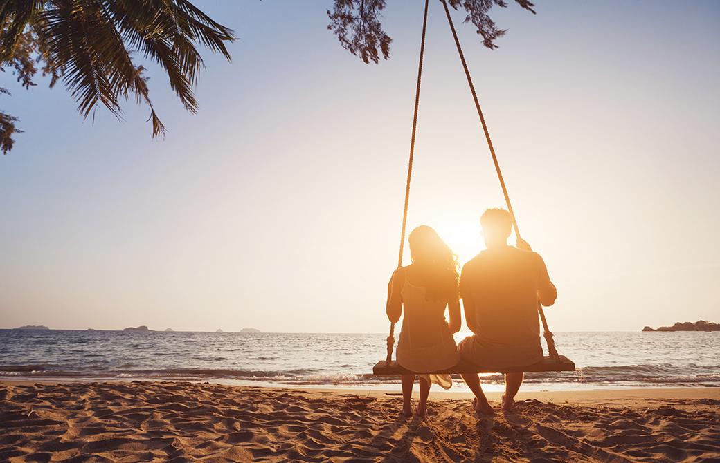夕暮れ時の海辺の砂浜で肩を寄せ合ってブランコに乗る男女