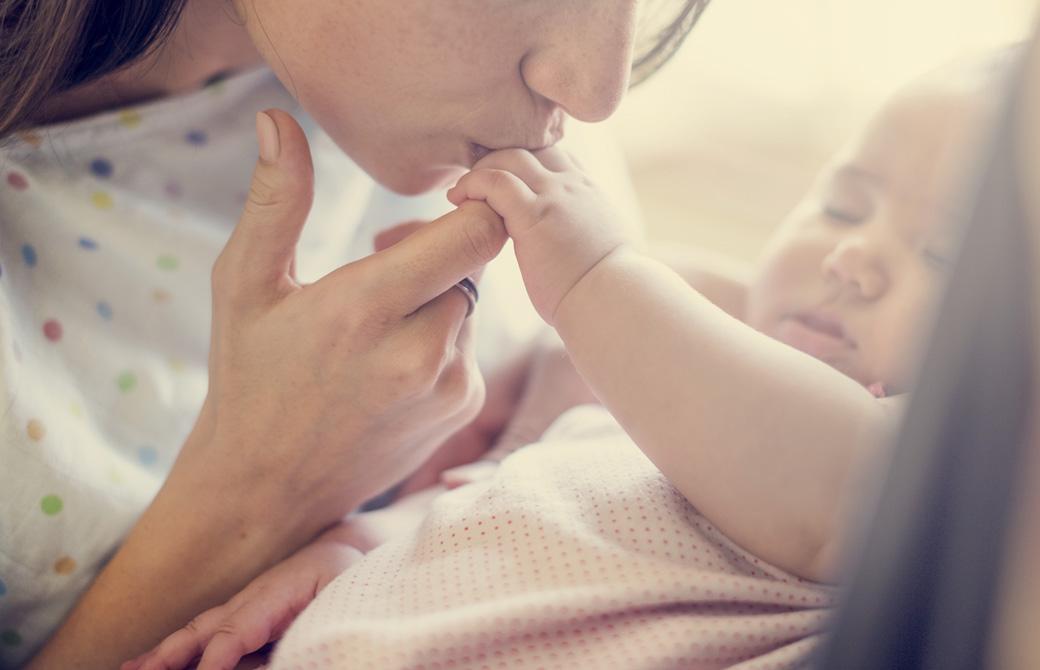 赤ちゃんの指先に優しくキスする母親