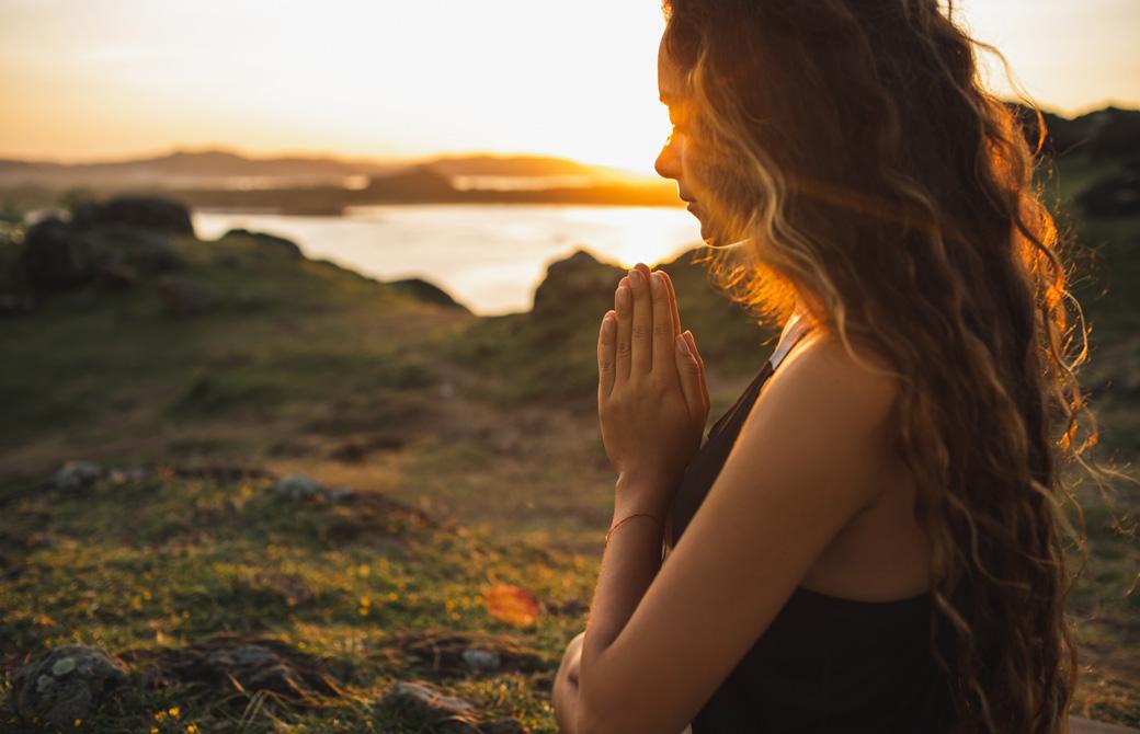 自然の中で手を合わせて祈る女性の横顔
