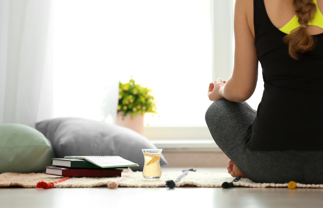 断食のレモン水を置いて瞑想をする女性の後ろ姿