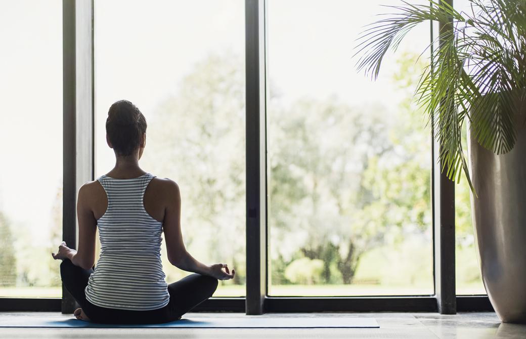 室内の窓際でヨガマットの上にあぐらで座りこちらに背を向けて瞑想をしている女性