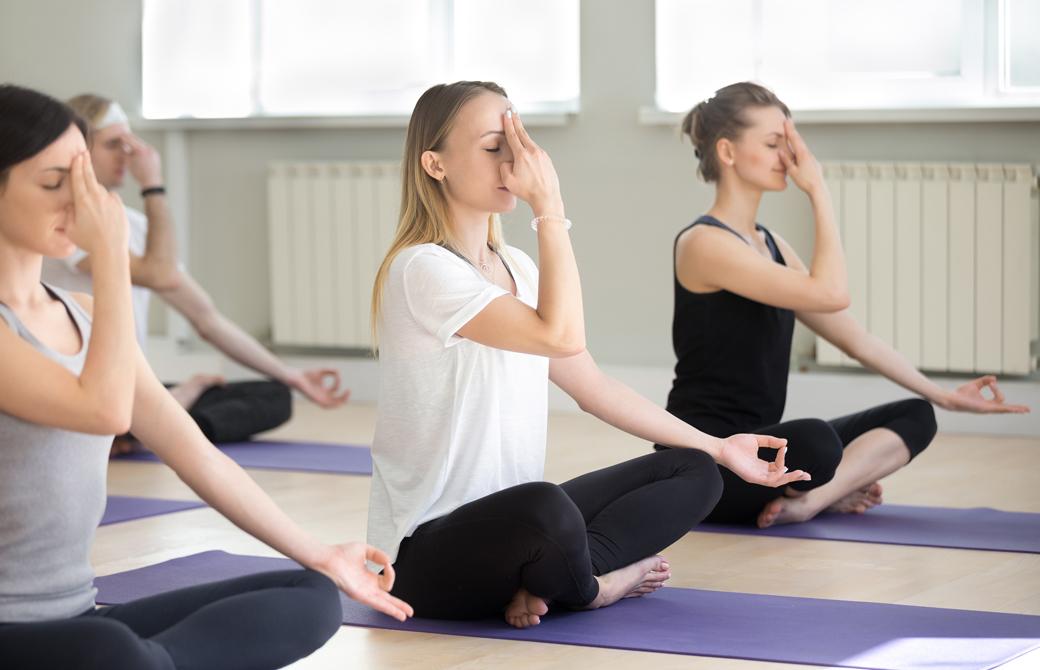 ヨガクラスで生徒達が片手を使った体を冷やす呼吸法の練習をしている