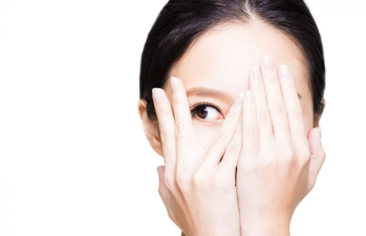 両手で顔を覆い右目だけのぞかせて横を見ている女性