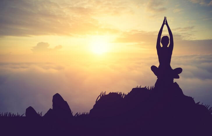 小高い岩の上で朝日に向ってあぐらで座り腕を頭上に伸ばして合掌している女性