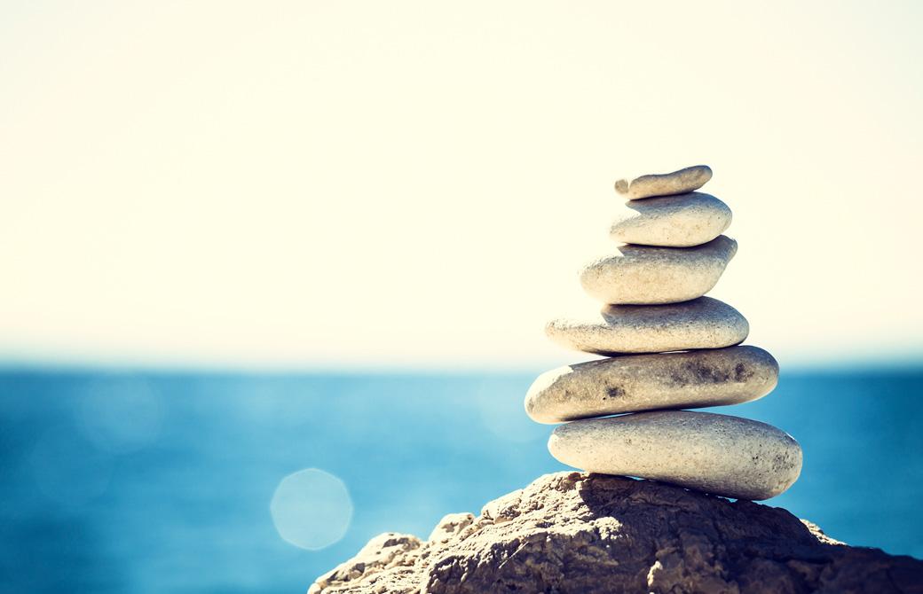 海に面した岩の上にバランスよく積まれた6個の石