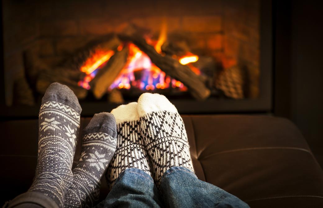 暖炉の前で靴下を履いて足を並べているカップル