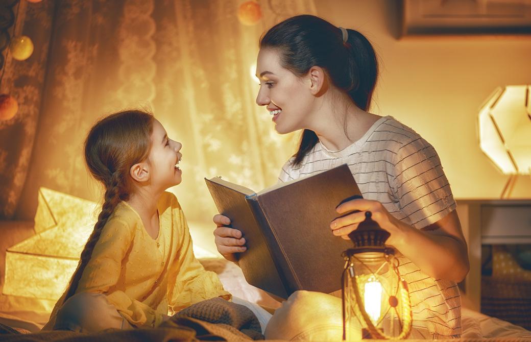 母親が幼い娘に微笑み合いながらベッドで絵本を読んであげている