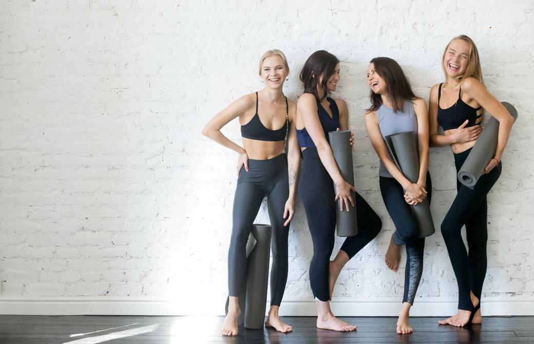 4人の女性がヨガウェアでヨガマットを持って壁にもたれて微笑み合っているところ