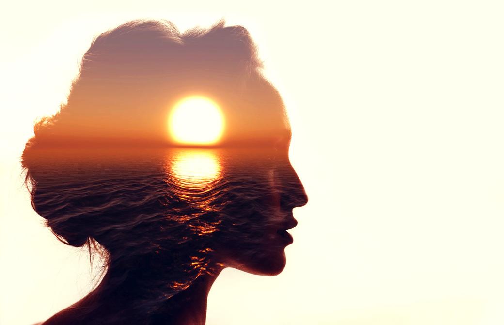 女性の横顔のシルエットの中に美しい夕日が沈んでいる