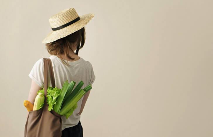 エコバッグに野菜を入れて肩にかけている帽子をかぶった女性の後ろ姿