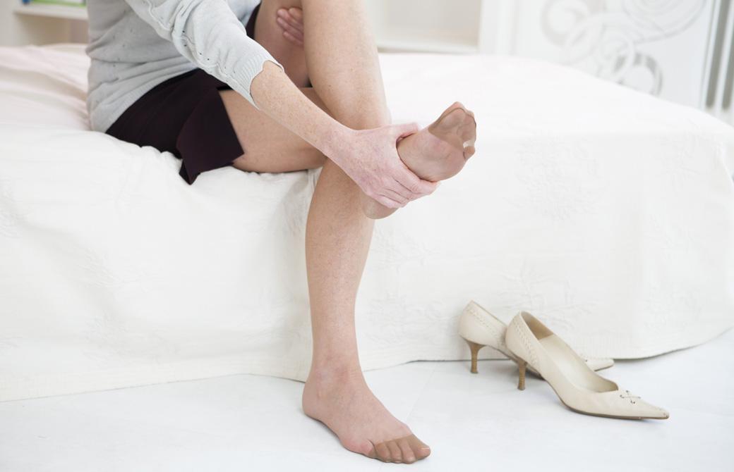 パンプスを脱いだ女性がベッドに座って足を触っている