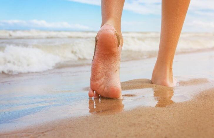 裸足でビーチを歩いている女性の足もと
