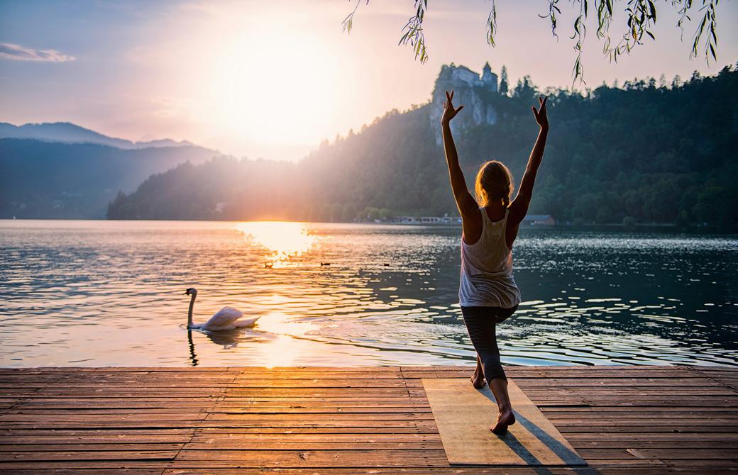 湖のほとりでヨガアサナをする女性と湖面を泳ぐ白鳥
