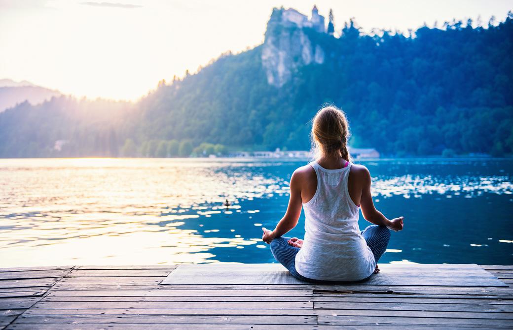湖のほとりで瞑想をする女性