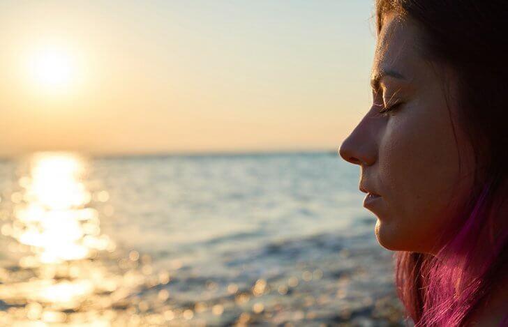 夕陽の海辺で目を閉じている女性の横顔