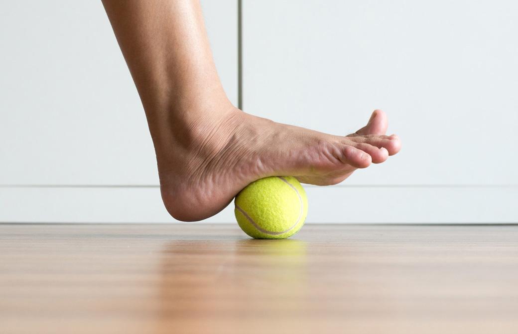 テニスボールに裸足の片足を乗せているところ