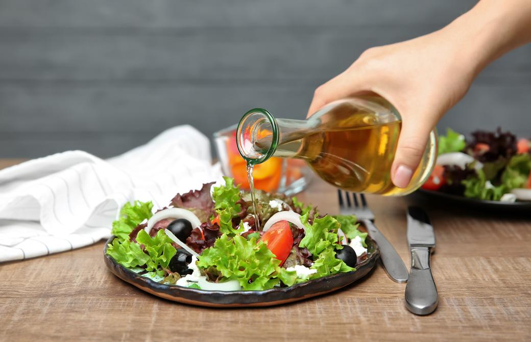 サラダに酢をかけている人の手