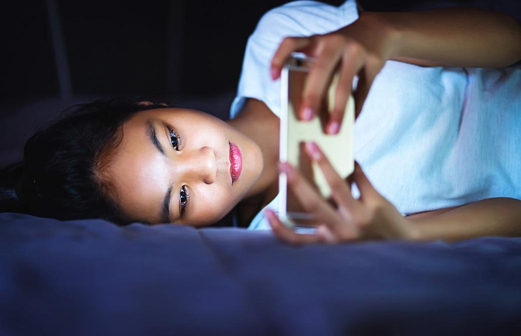 ベッドに横になりスマートフォンを操作しているアジア女性