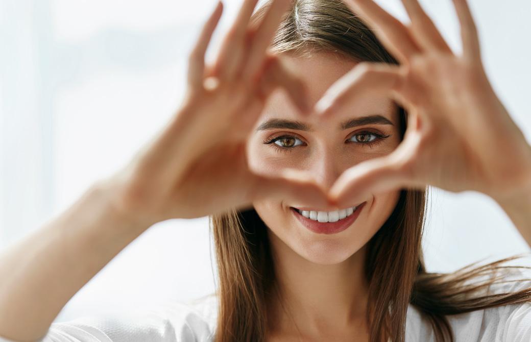 顔の前で指でハート型をつくりこちらを覗いている笑顔の女性