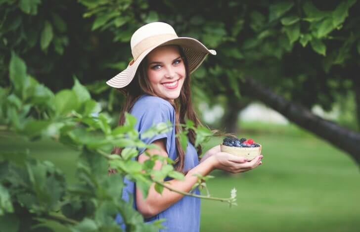 木々に囲まれブルーベリーの入った器を持って微笑む女性