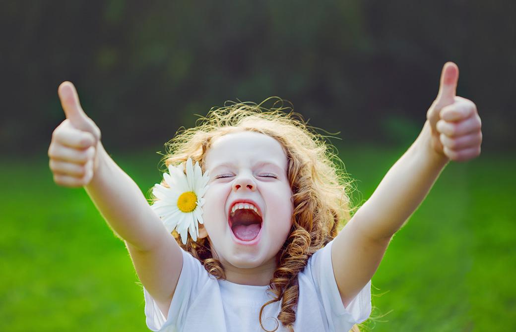 花を耳にさしてオーケーサインで笑う子ども
