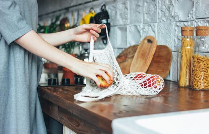 調理台の上でエコバッグからリンゴを取り出している女性の腕