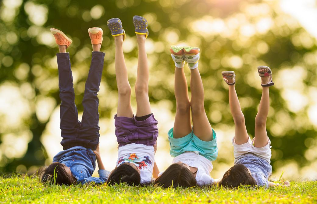 芝生の上で肩立ちのポーズをしている子どもたち
