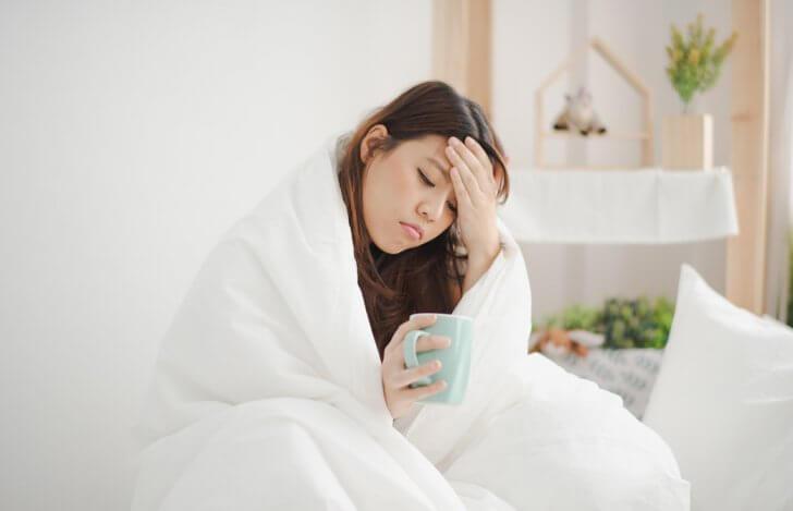 ベッドの上で毛布にくるまりおでこをおさえて具合悪そうにコーヒーカップを手にする女性