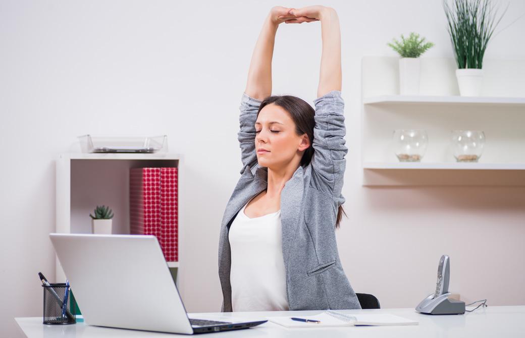 デスクで仕事中に両腕を伸ばして肩のストレッチをしている女性