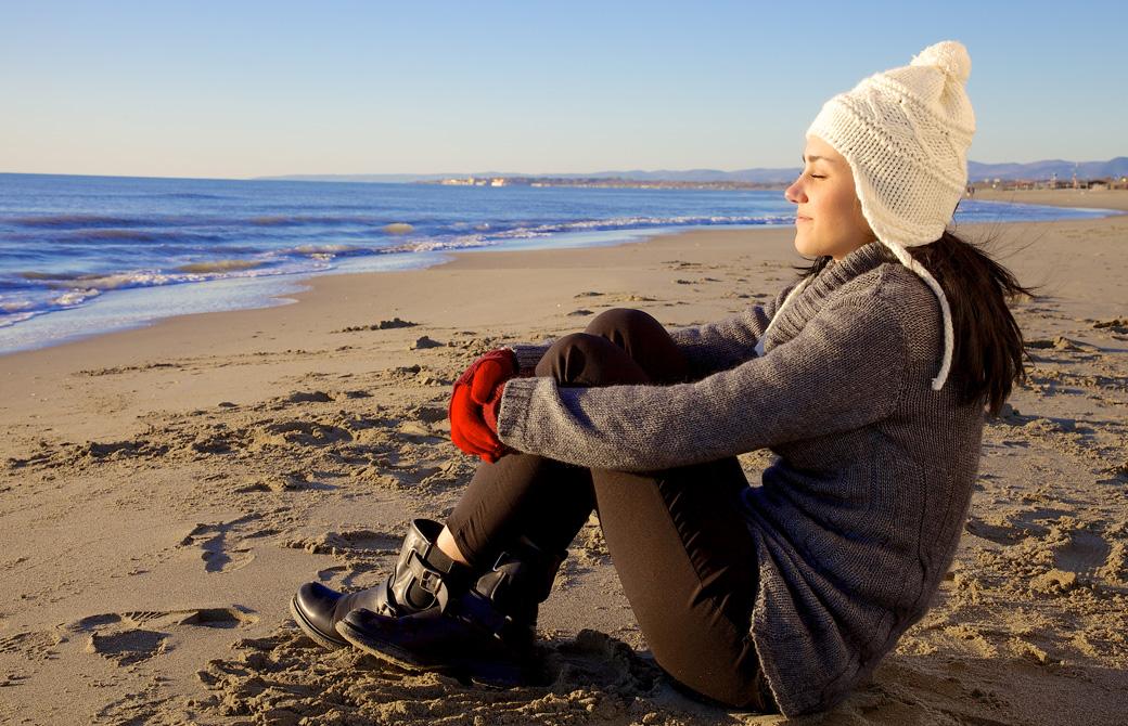 冬の海岸で日を浴びている女性