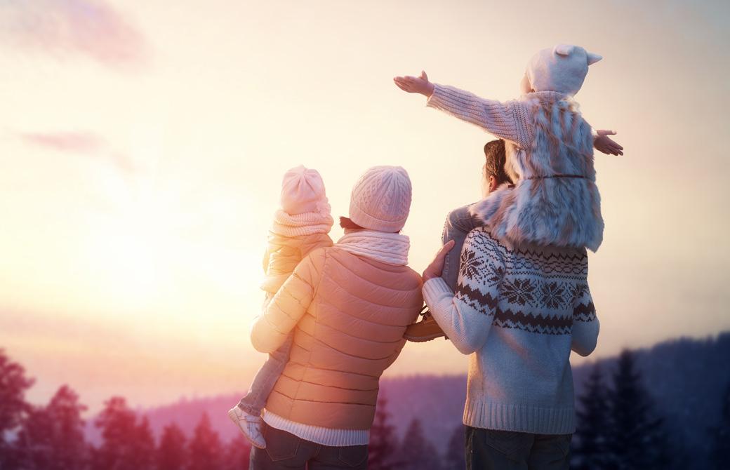 太陽に向かって腕を広げいてる少女を肩車する父親と横で赤ん坊を抱っこしている母親
