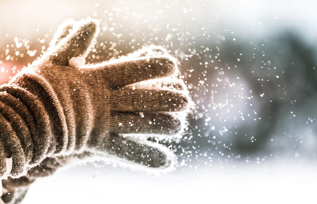 手袋をつけた両手が雪をはらっている