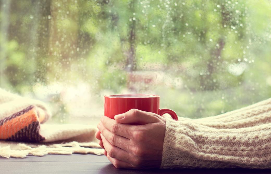 温かい飲み物の入ったカップを両手で包み込む人