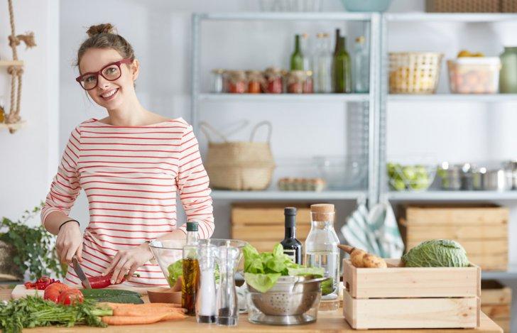 キッチンで野菜を手にして微笑む眼鏡をかけた女性