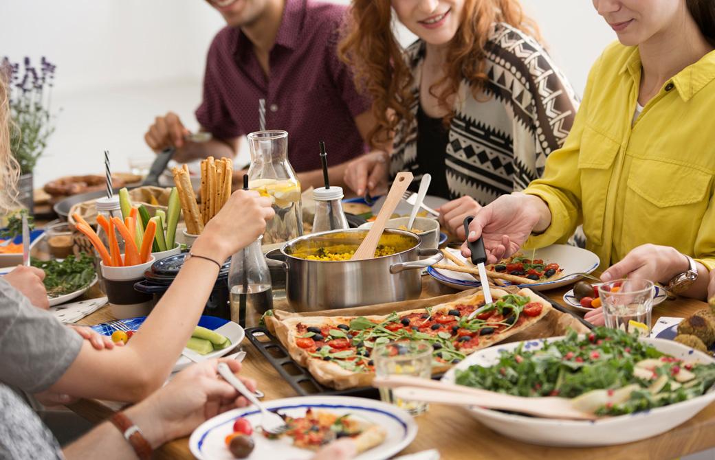 野菜に彩られた食卓を囲むひとたち