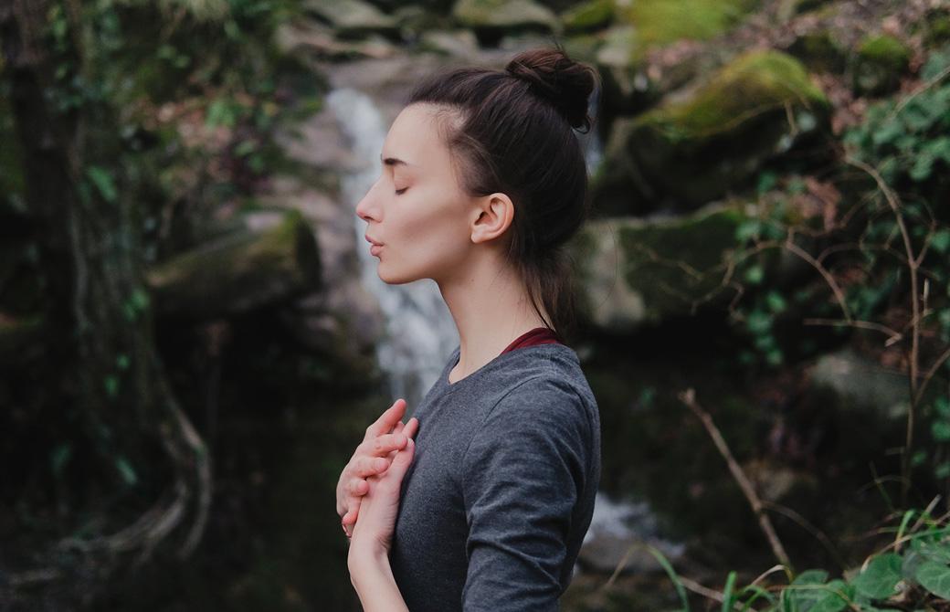 滝の前で両手を胸に当て目を閉じている女性の横姿