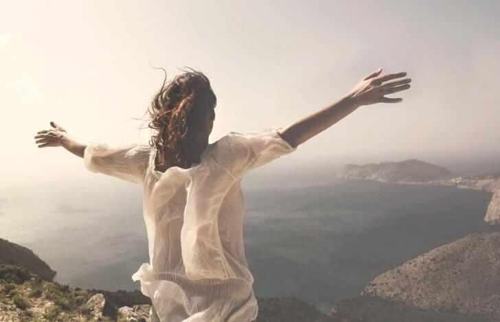 海に臨む山頂で両腕を広げている女性の後ろ姿