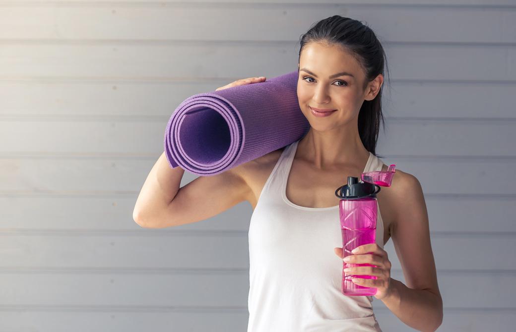 パープルのヨガマットとピンクの水ボトルを持って微笑む女性
