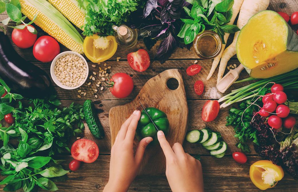 新鮮でカラフルな野菜たちとピーマンを切ろうとしている女性の手
